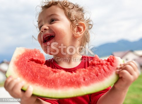 Little girl eating watermelon in the garden, laughing and looking sideways