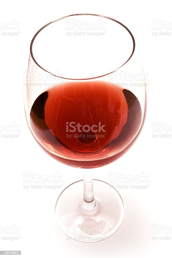 Almost empty glass of red wine on a white background stock photo