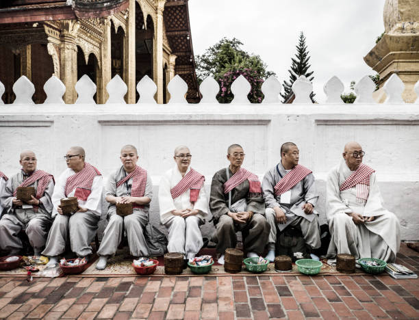 Alms giving ceremony Luang Prabang Laos People waiting at the street in the morning for Buddhist monks collecting alms  in Luang Pragang Laos. Every morning the monks walk through the streets of Luang Prabang too collect alms of local residents and tourists of the town. alas stock pictures, royalty-free photos & images