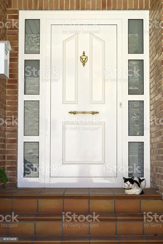 Almudevar (Spain): White door and cat royalty-free stock photo
