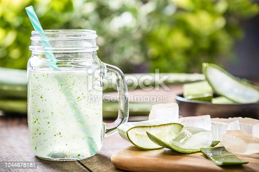 Front view of a drinking glass full of an aloe vera drink surrounded by some aloe vera crystals and sliced leaves. A black bowl full of sliced aloe vera leaves is defocused on the background. Predominant color are green and brown. Studio shot taken with Canon EOS 6D Mark II and Canon EF 24-105 mm f/4L