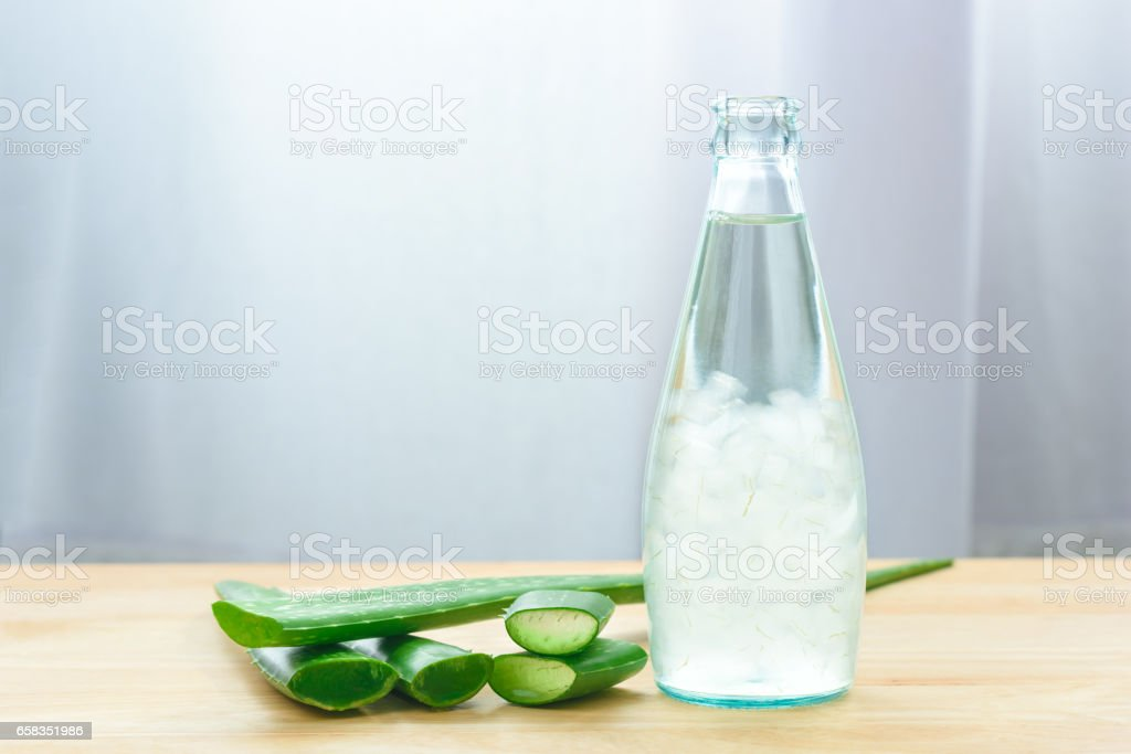 Aloe vera juice in bottle with fresh aloe vera leaves on wooden background stock photo