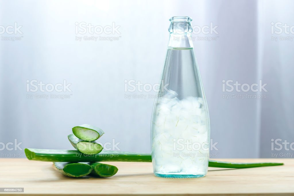 Aloe vera juice in bottle with fresh aloe vera leaves on wooden background royalty-free 스톡 사진