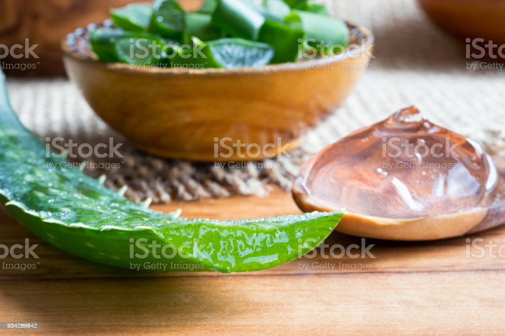 Aloe vera leaf, with aloe vera gel and slices in the background stock photo