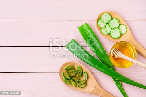 Green fresh aloe vera leaf with cucumber slice in wooden spoon and honey isolated on pink wood table background. Natural herbal medical plant, skincare, health and beauty spa concept. Flat lay.