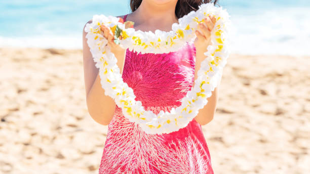 aloha greeting with hawaii flower lei on the beach - floral garland stock pictures, royalty-free photos & images