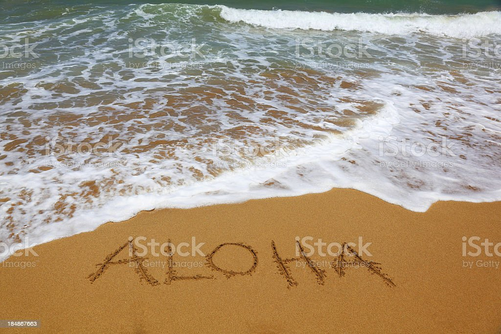 Aloha written in sand on the beach with tide coming in stock photo