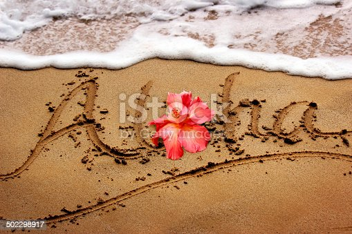 Aloha written in the sand with a hibiscus flower and the surf approaching in Maui, Hawaii.