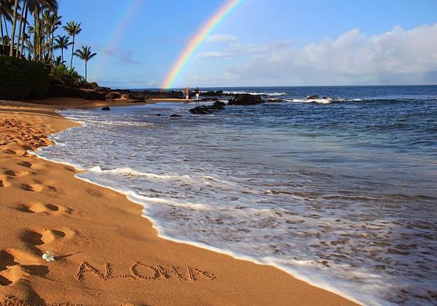 Aloha written on Maui Hawaii beach sand with double rainbow stock photo