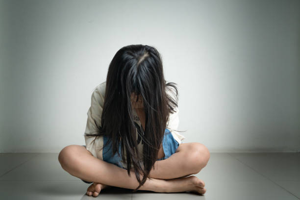 Alone and scared, sad depressed children close her face in the dark room after being bullied stock photo