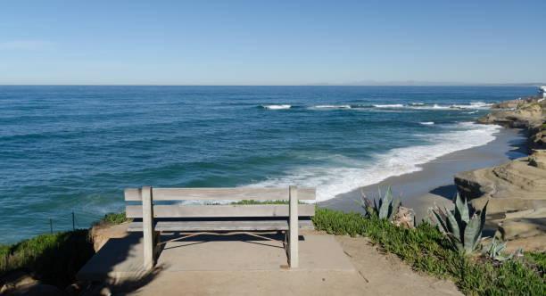 Alone bench facing surf near Childrens Pool in La Jolla, Southern California stock photo