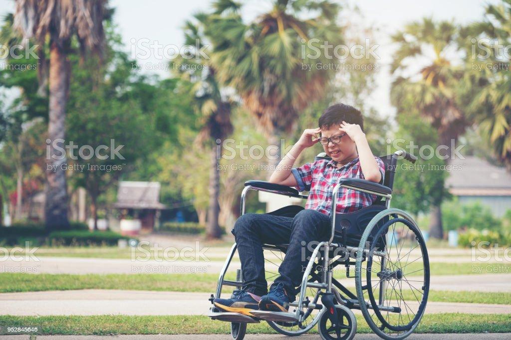 Allein Junge im Rollstuhl mit einer Kopfschmerzen im park – Foto