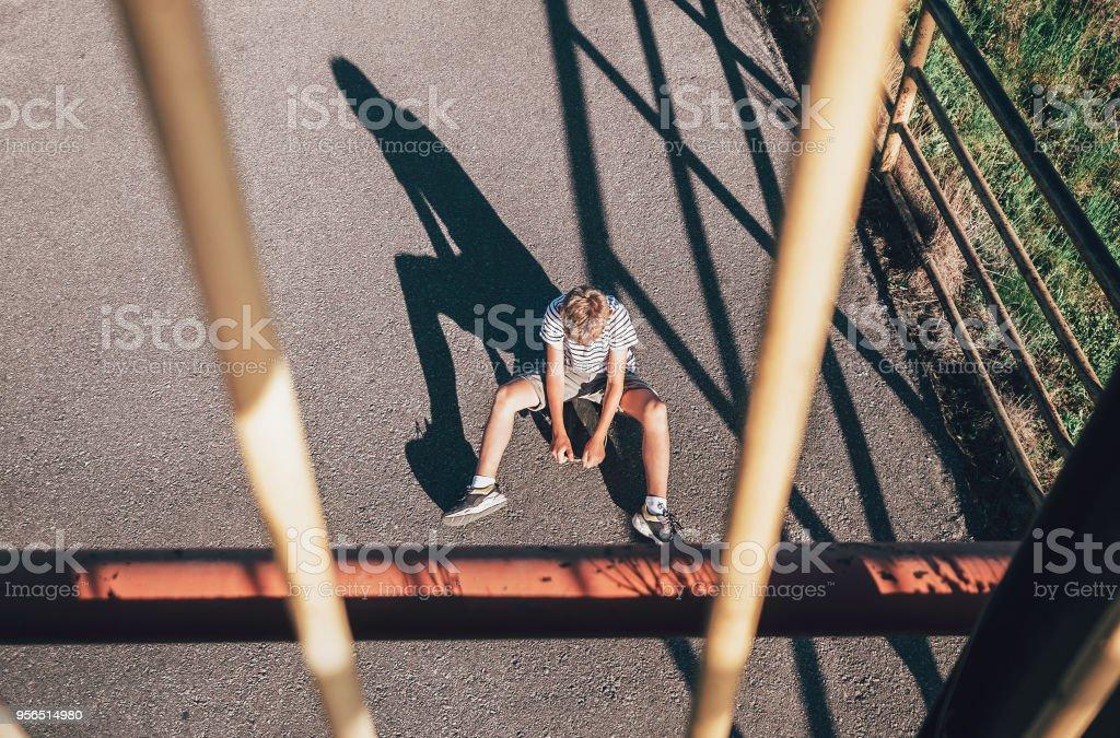 Allein junge ohne Freunde sitzt auf Skateboard. Kind-Einsamkeit-Konzept-Bild - Lizenzfrei Aktiver Lebensstil Stock-Foto