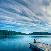 A woman sits on the edge of a jetty at peaceful lake with a dramatic sky.