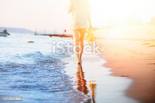 Alone depressive young woman walking on the beach