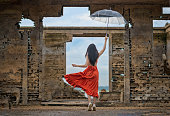 woman fashion dress cheerfully jump on the retro old cottage house in the lake, holding umbrella under raining season\