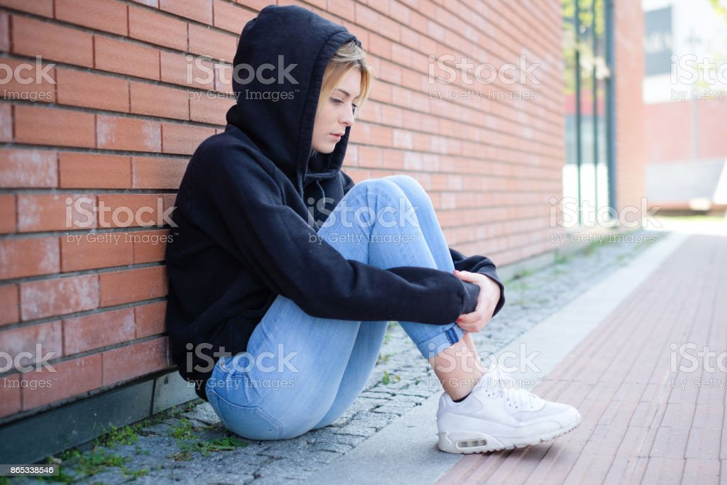 Alone girl portrait with hooded sweatshirt next urban street wall stock photo