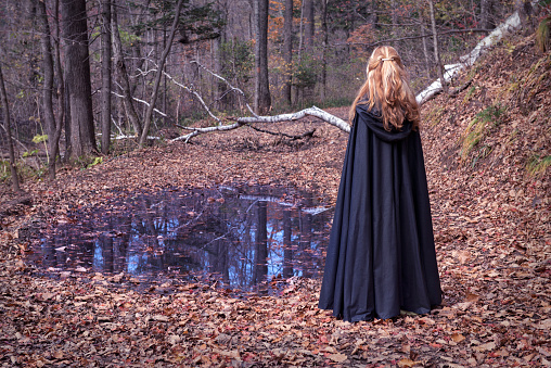 Alone girl wearing black mantle standing by the water