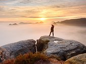 istock Alone hiker in red cap stand on peak of sandstone rock in rock empires park and watching over the mist 924411750