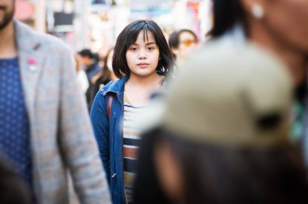 Alone in a crowd A young woman standing in the middle of a crowded street, looking at the camera. spectator stock pictures, royalty-free photos & images
