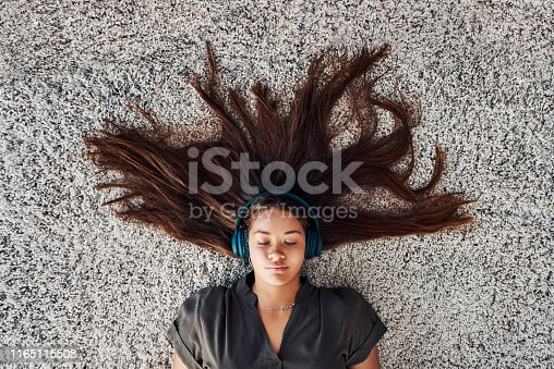 High angle shot of a young woman relaxing on the floor and listening to music at home