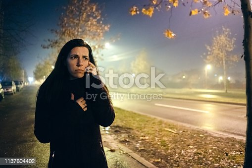 Young woman is using phone, scared of walking down the dark street and surrounded with fog
