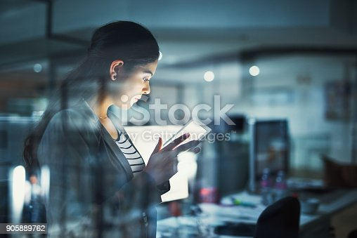 Shot of a young businesswoman working late in the office