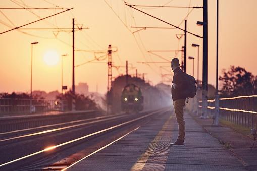 Alone man with backpack waiting at railroad station platform at sunrise.