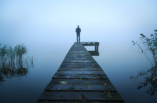 alone on a jetty - grief stock photos and pictures