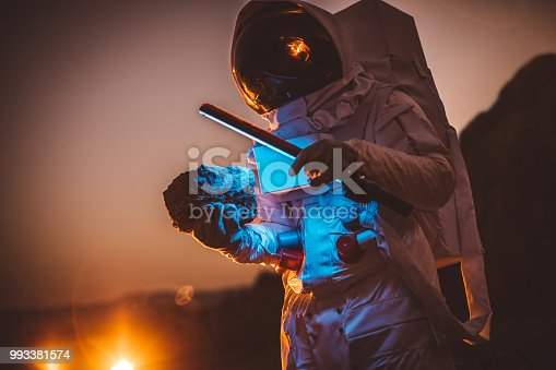 One man, astronaut exploring the land on the other planet at night, holding a lamp.