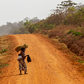 Hoima, Uganda - February 29, 2012: Alone pregnant woman walking on the dirt road with baby and She is carrying black nylon bag and brooms on her head. She is looking at camera and She is smiling.