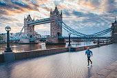 Alone runner in empty streets of london in Coronavirus, Covid-19 quarantine time. Tower Bridge in background