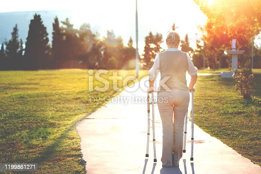 Alone senior woman with walking zimmer