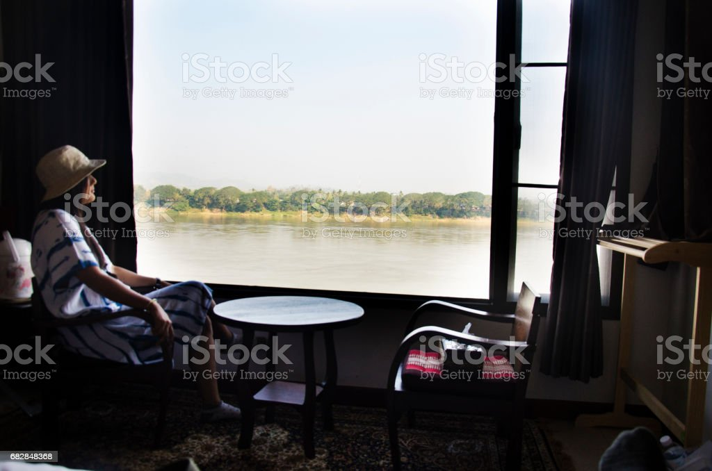 Alone thai woman sitting on chair looking view landscape and flowing of Mae Khong river Lizenzfreies stock-foto
