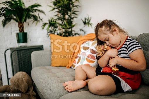 Girl with Down's syndrome playing with doll at home