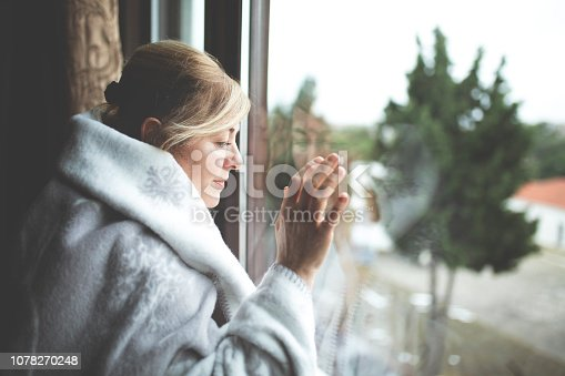 543048812 istock photo Alone woman day dreaming by the window 1078270248