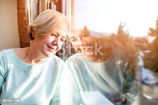 543048812 istock photo alone woman day dreaming by the window 897821738