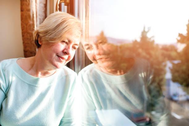 journée de la femme seul rêve par la fenêtre - une seule femme senior photos et images de collection