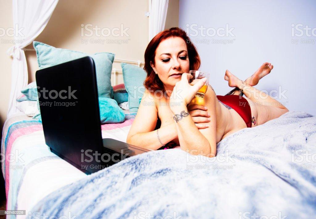 Seule femme se détend sur un lit avec ordinateur portable et boisson - Photo