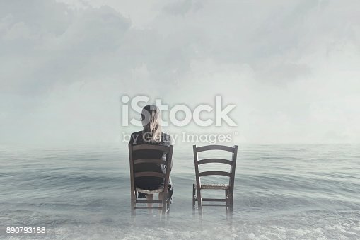 istock alone woman sitting next to her lover's empty chair 890793188