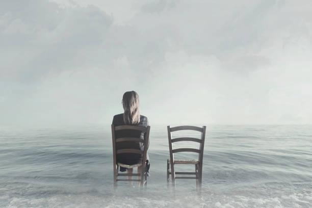 allein Frau saß neben ihrem geliebten leeren Stuhl – Foto