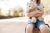 """""""Color photo of a sad, lonely 6-7 year old girl hugging an old, raggedy teddy bear while sitting on an old suitcase on a dirt road outside."""""""