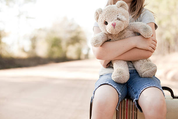 alone young girl hugging old, raggedy teddy bear - teddy bear stock photos and pictures