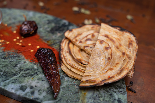 Aloo Paratha / Indian Potato stuffed Flat bread in white plate. on wooden table.Homemade Indian Naan Flat bread made with Whole Wheat.on wooden table stock photo.Aloo Paratha / Indian Potato stuffed Flat bread in white plate. on wooden table.