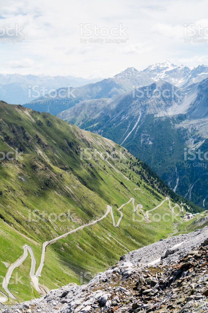 Alp road surrounded by blue alp high mountains and green hills stock photo