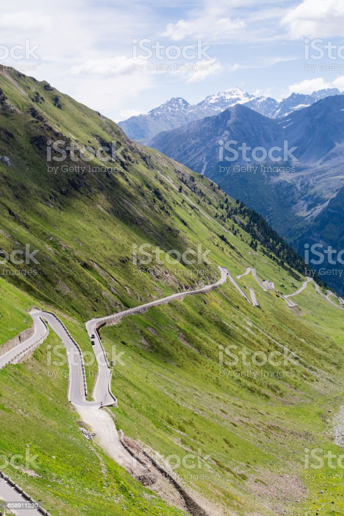 Alp road surrounded by blue alp high mountains on background. stock photo