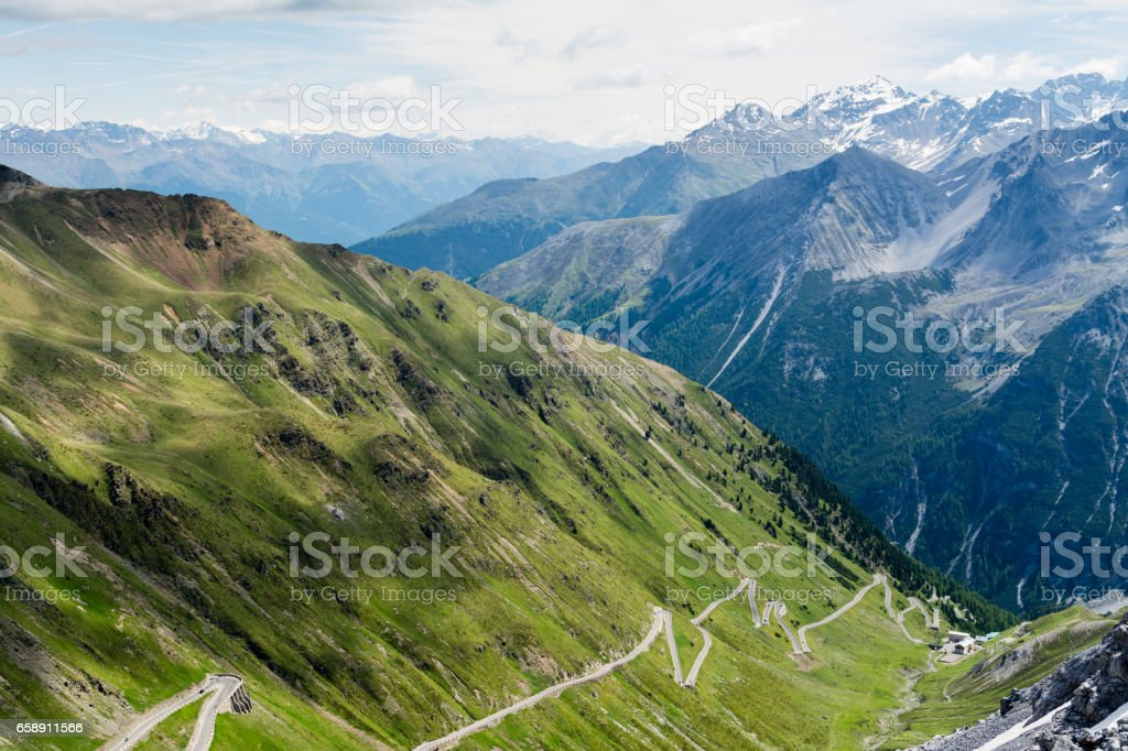 Alp road surrounded by green hills and blue alp high mountains on background. stock photo