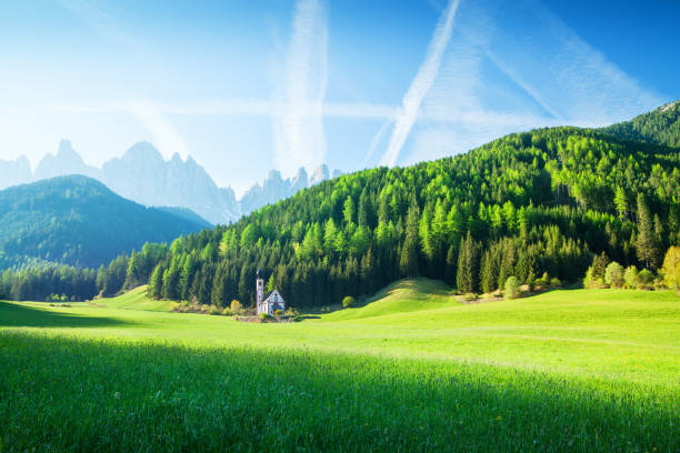 Alpen Landscape - Green field, Village Val di Funes Villnöss and Mountains stock photo