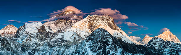 Alpenglow illuminating Mt Everest summit after sunset Himalaya mountain panorama Lenticular clouds caressing the iconic pyramid peak of Mt. Everest (8848m) as delicate alpenglow light illuminates the south west face and the summits of Nuptse (7861m), Lhotse (8516m) and Makalu (8463m) in this vibrant Himalaya mountain panorama deep in the Sagarmatha National Park of Nepal, a UNESCO World Heritage Site. ProPhoto RGB profile for maximum color fidelity and gamut.  lenticular cloud stock pictures, royalty-free photos & images