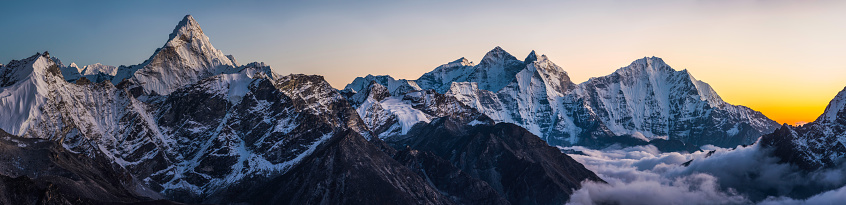 Delicate sunset light illuminating the dramatic snow capped summits and fluted glaciers high above the clouds of the Khumbu valley, from the iconic spire of Ama Dablam (6812m) to the pinnacles of Kangtega (6782m) and Thamserku (6623m) deep in the Everest National Park of Nepal, a UNESCO World Heritage Site.